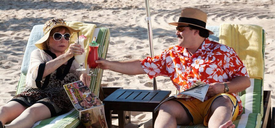 Two characters from the movie Bernie siting on beach