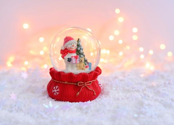 A snow globe with a snowman inside holing a Christmas tree