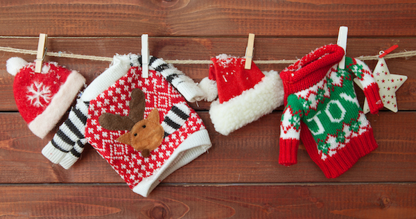 Little knitted christmas pullovers on a wooden background