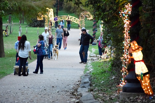 People and their pets walking along the Bastrop River of Lights trail.