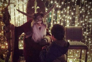 Krampus scaring a small boy at Scream Hollows Twisted Christmas in Bastrop County in Texas.