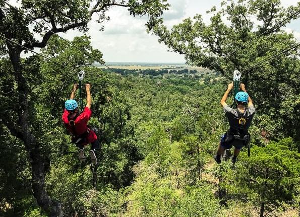 Two people zip lining down dual lines at Zip Lost Pines near Cedar Creek, Texas