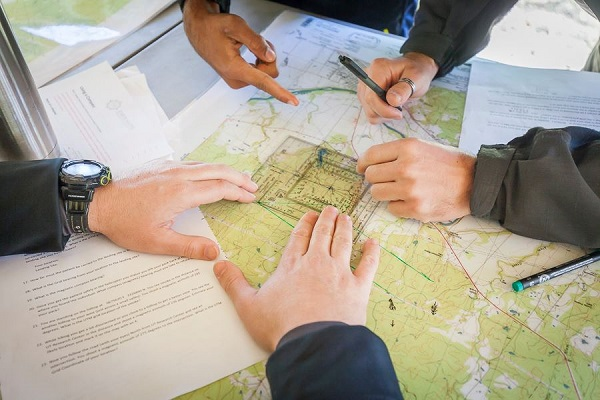 Hands marking an area on a map.
